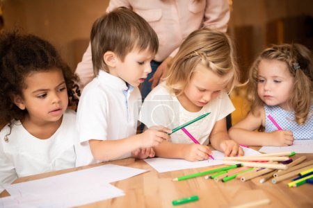 Photo for Cropped image of educator standing near multicultural kids drawing in kindergarten - Royalty Free Image
