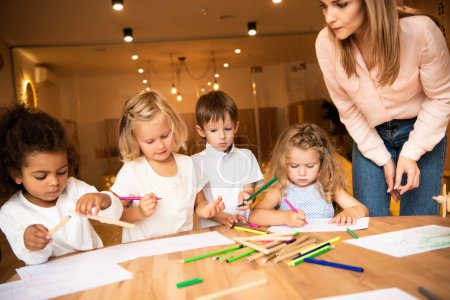 Photo for Educator looking at multiethnic group of children drawing in kindergarten - Royalty Free Image