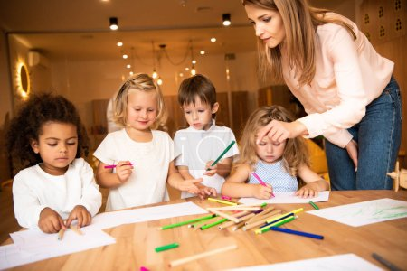 Photo for Educator looking at multiethnic children drawing in kindergarten - Royalty Free Image