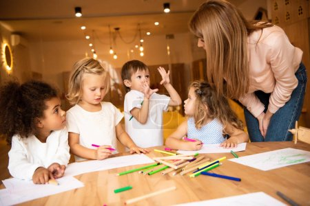 Photo for Multiethnic children drawing in kindergarten, educator looking at gesturing boy - Royalty Free Image