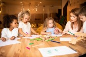 educator drawing together with multicultural kids in kindergarten