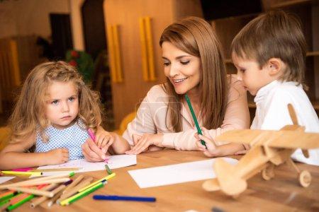 Photo pour Éducateur de dessin avec les enfants à l'école maternelle de sourire - image libre de droit