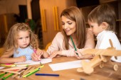smiling educator drawing together with kids in kindergarten