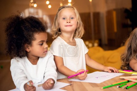 Photo for Adorable multicultural children drawing together in kindergarten - Royalty Free Image