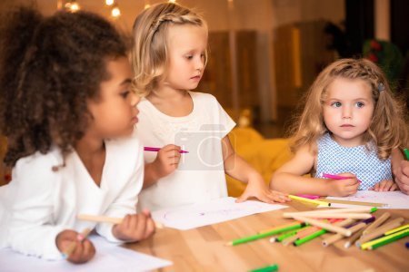 Photo for Multiethnic kids drawing together with felt tip pens in kindergarten - Royalty Free Image