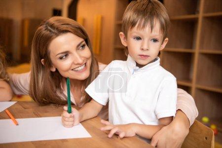 Foto de Educador niño adorable abrazando a la mesa en el jardín de la infancia sonriente - Imagen libre de derechos