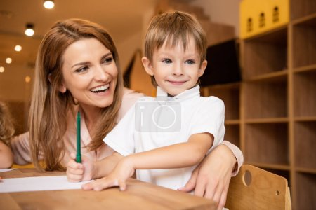 Photo for Happy educator hugging adorable boy at table in kindergarten - Royalty Free Image