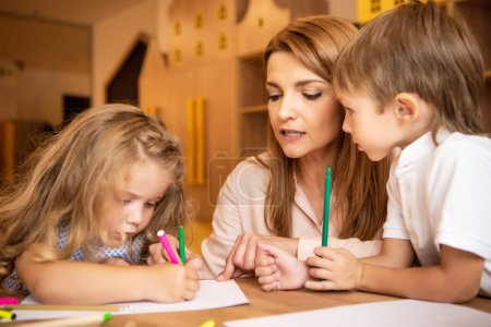 educator and children drawing together in kindergarten