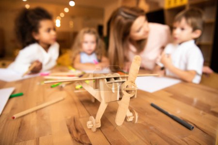 educator and multiethnic kids drawing in kindergarten, wooden plane on foreground