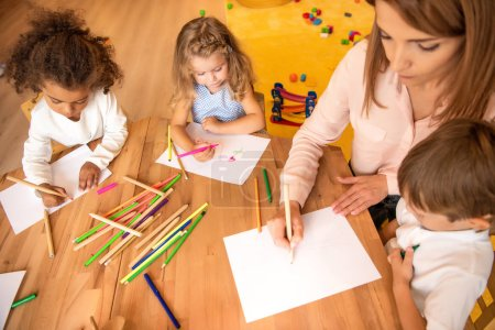 high angle view of educator and multiethnic kids drawing in kindergarten