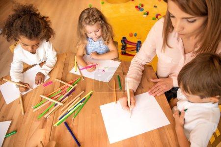 Photo pour Vue grand angle éducateur et multiethniques enfants dessin à l'école maternelle - image libre de droit