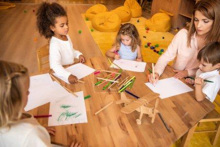 Photo pour Vue grand angle éducateur et multiculturelles enfants dessin à l'école maternelle - image libre de droit