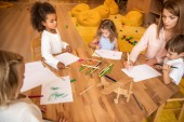high angle view of educator and multicultural children drawing in kindergarten