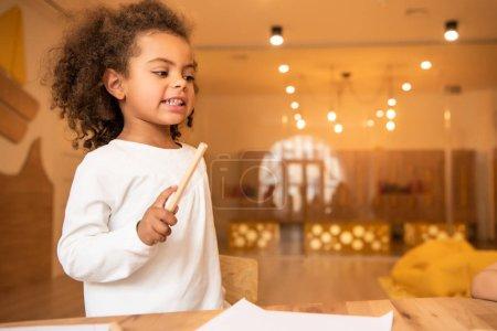 african american kid holding felt tip pen in kindergarten