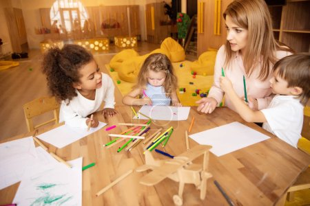 Photo for Educator talking to multicultural kids drawing at table in kindergarten - Royalty Free Image