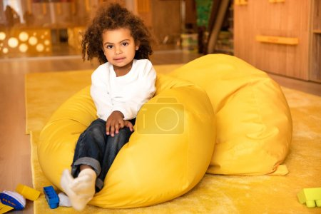 adorable african american kid sitting on bean bag chair in kindergarten and looking at camera
