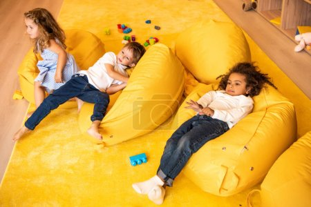 high angle view of multicultural children lying on yellow bean bag chairs in kindergarten