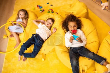 high angle view of multiethnic kids lying on bean bag chairs with toys in kindergarten