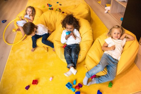 high angle view of multicultural kids lying on bean bag chairs in kindergarten