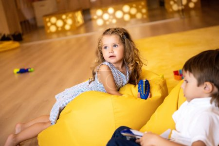 Photo for Adorable children with toys lying on yellow bean bag chairs in kindergarten and looking away - Royalty Free Image