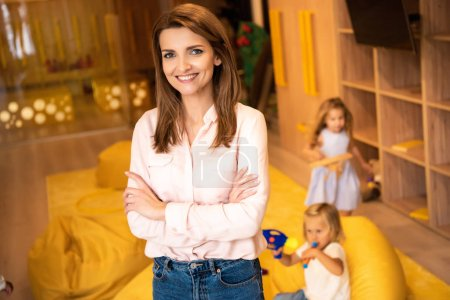 smiling educator standing with crossed arms and looking at camera in kindergarten, kids playing on background