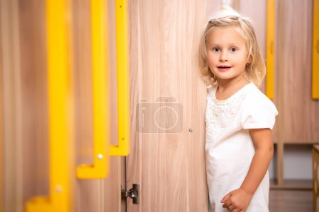 adorable kid standing near open locker and looking at camera in kindergarten cloakroom