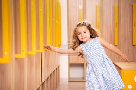 Photo for Adorable kid standing in kindergarten cloakroom and taking locker handle - Royalty Free Image