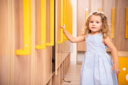 Photo for Smiling adorable kid opening locker in kindergarten cloakroom and looking at camera - Royalty Free Image