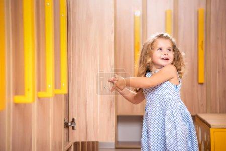 smiling adorable kid opening locker in kindergarten cloakroom