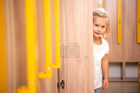 Photo for Cheerful adorable kid standing in kindergarten cloakroom and looking out from locker - Royalty Free Image