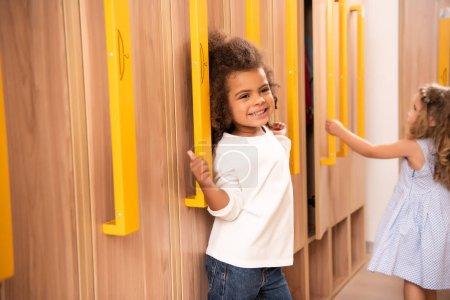 happy multicultural kids standing near lockers in kindergarten cloakroom