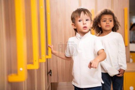 Photo for Multiethnic kids standing in kindergarten cloakroom - Royalty Free Image