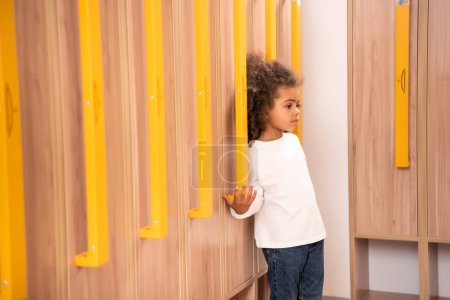 adorable african american kid standing near wooden lockers in kindergarten cloakroom