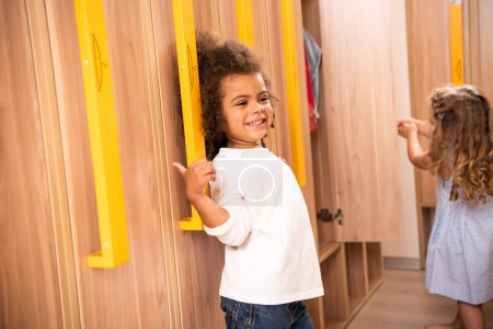 smiling multicultural kids standing near lockers in kindergarten cloakroom