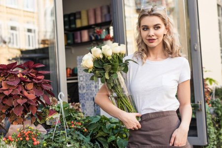beautiful florist holding jar with white roses near flower shop and looking away