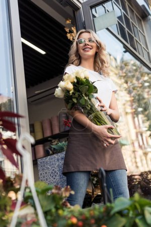 low angle view of beautiful happy florist going out from flower shop with roses in jar