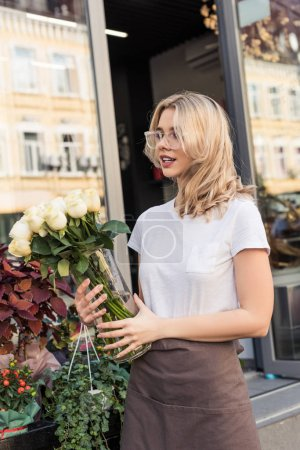 attractive florist holding jar with white roses near flower shop and looking away