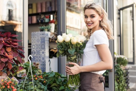 attractive florist holding jar with white roses near flower shop and looking at camera