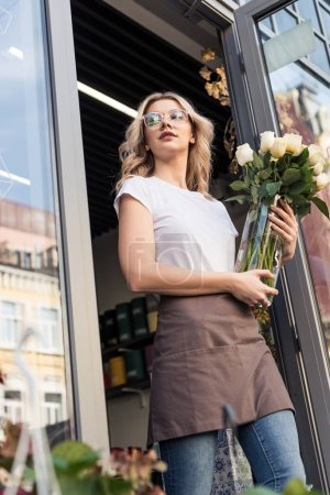 low angle view of beautiful florist going out from flower shop with roses in jar