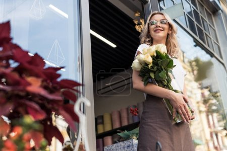 low angle view of attractive florist going out from flower shop with roses in jar