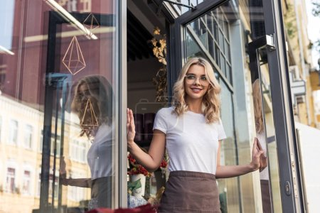 smiling attractive florist opening door and going out from flower shop