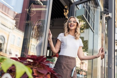 low angle view of happy attractive florist opening door and going out from flower shop