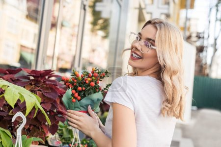 smiling attractive florist holding potted plant near flower shop