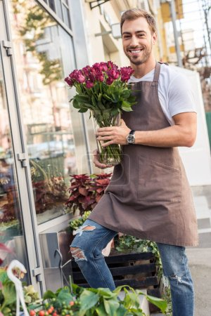 handsome smiling florist holding roses in jar near flower shop and looking at camera