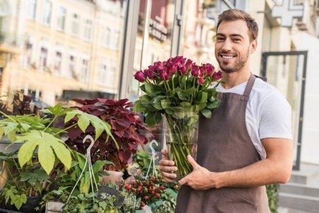 handsome smiling florist holding roses in jar near flower shop
