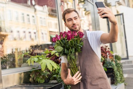 handsome florist holding roses in jar and taking selfie with smartphone near flower shop