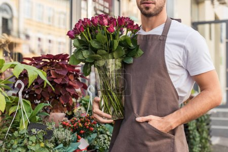 cropped image of florist holding glass jar with burgundy roses near flower shop