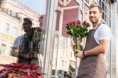 low angle view of handsome florist holding glass jar with burgundy roses near flower shop and looking at camera