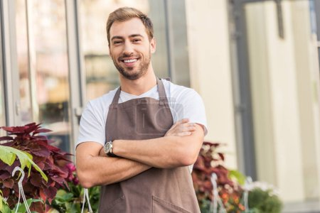 smiling handsome florist in apron standing with crossed arms near flower shop and looking at camera