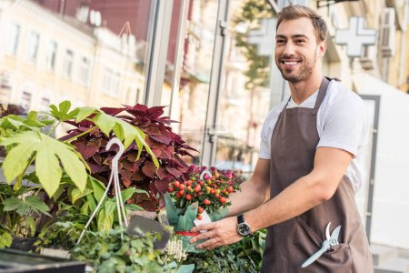 handsome smiling florist taking potted plant with red berries near flower shop